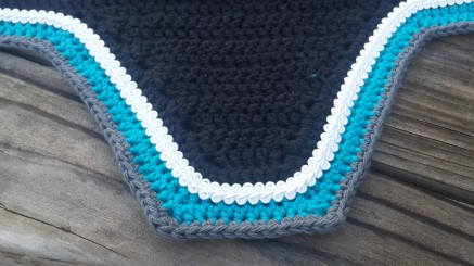 Black, turquoise, grey with white scroll cord.